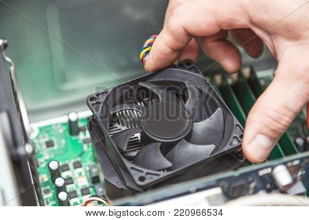 Technician hands installing CPU cooler fan on a computer pc motherboard.