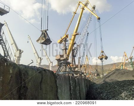Cargo industrial port, port cranes. Loading of anthracite. Transportation of coal. Heap of coal.