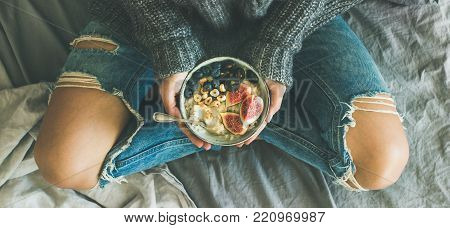 Healthy winter breakfast in bed. Woman in sweater and jeans holding rice coconut porridge with figs, berries, hazelnuts, top view, wide composition. Clean eating, vegetarian, comfort food concept