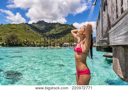 Luxury travel destination bikini woman taking an outdoor shower at luxury resort hotel overwater bungalow in Tahiti. Vacations in paradise Asian girl showering after swim.