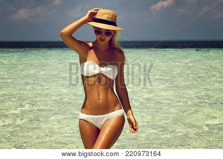 Summer girl model with tanned sexy body. Posing in the white swimsuit on the beach of the tropical island.