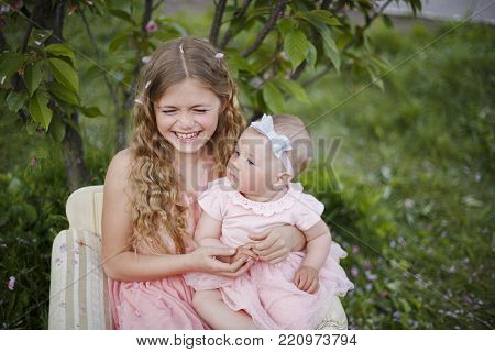 Two happy little sisters love and hug in beautiful park. Cute little girls in pink dress play in spring garden. Adorable child walk and laugh on green meadow