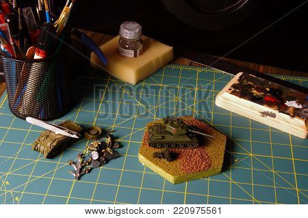 Hobbyist desk with various brushes, paint and tools with model tanks being built