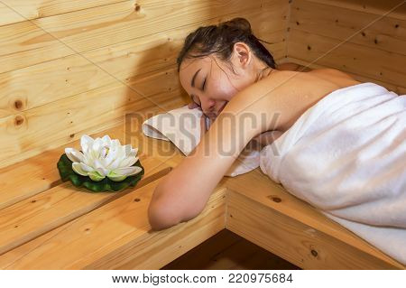 Beautiful Young asian girl sleeping relax, lying in sauna cabin in spa sauna room.