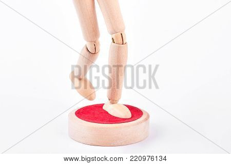Legs of human wooden dummy on white. Cropped image of wooden dummy standing on stand with one leg.