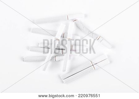 Pile of tobacco cigarettes, white background. Tobacco cigarettes with filter over white background. Smoking addiction concept.