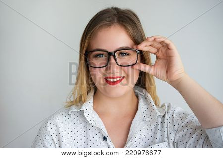 Happy pleased student girl adjusting eyeglasses and looking at camera. Cheerful confident smart woman working in science. Intelligence concept