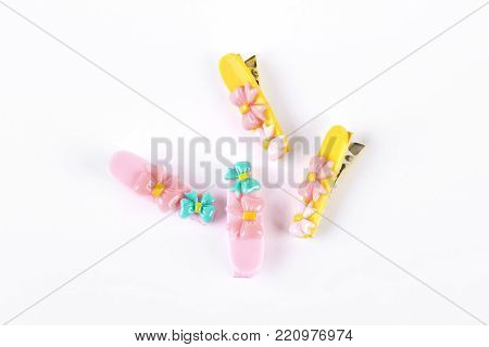 Two pairs of kid colorful hair clips. Pink and yellow hairpins for girls on white background. Childrens hair accessories.