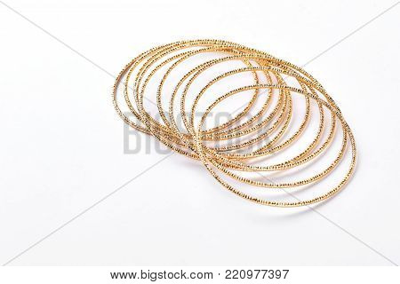 Set of golden adornment on white background. Collection of beautiful female bracelets isolated on white.