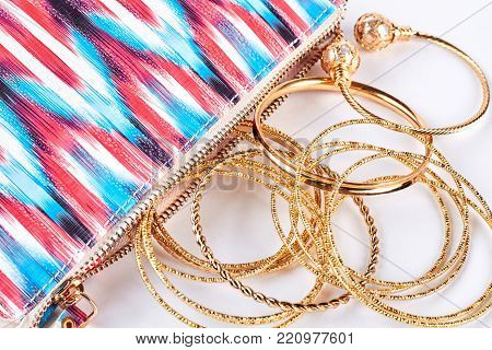 Close up of golden bangles and bag. Golden wrist bands and pink patterned cosmetics bag close up. Woman fashion accessory.