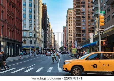 NEW YORK CITY - CIRCA 2017: Yellow taxi cab turning onto Broadway with people crossing the 8th Street intersection in Manhattan, New York City.
