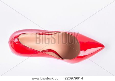 Female red shoe, top view. Woman lacquered shoe on high heel isolated on white background.