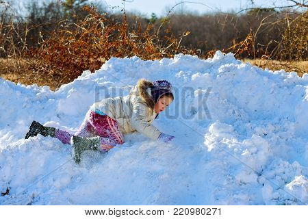 Happy kid playing in the snow near a forest Kids play outside winter season