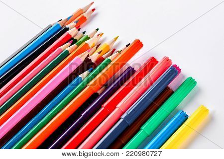 Rainbow collection of pencils for drawing. Big collection of pensils and markers of different colors, white background.
