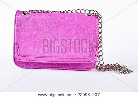 Female fashionable pink shoulder bag. Woman elegant leather clutch with chain isolated on white background. Lady glamour accessory.