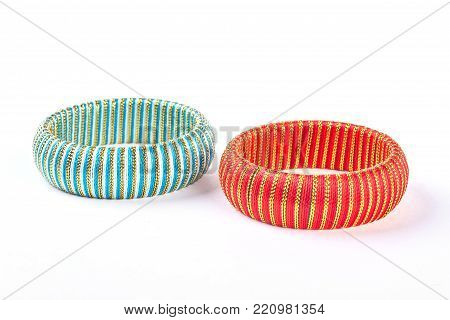 Two colorful fashion design bangles. Blue and red striped bracelets on white background. Woman fashion hand accessory.