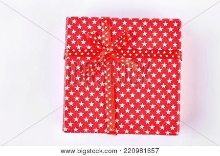 Red gift box on white background. Gift box wrapped in red paper with a pattern of white stars. Box with gift.