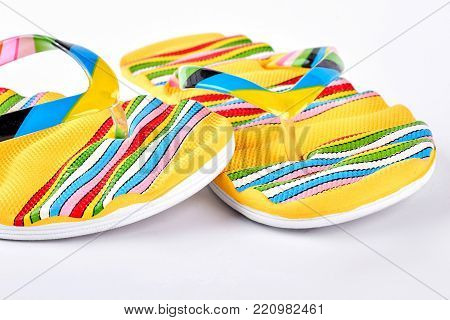 Striped flip flops on white background. Female fashion flip flops with colorful stripes isolated on white background. Summer brightful footwear.