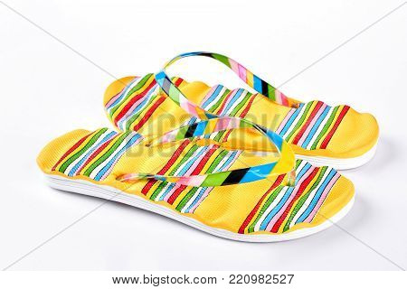 Summer fashion flip flops on sale. Female yellow striped flip flops on white background. Summer fashion concept.