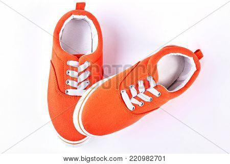 New collection of female sport shoes. New orange gumshoes isolated on white background, top view. Female txtile sneakers on sale.