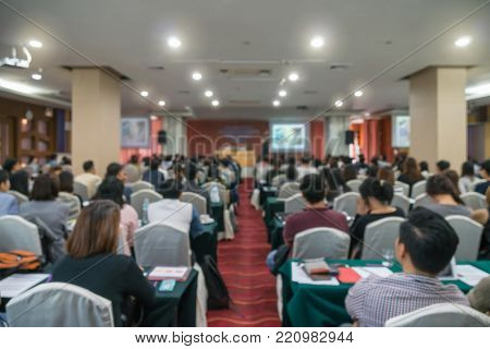 Abstract blurred photo of conference hall or seminar room which have Speakers on the stage with attendee background, Business meeting concept