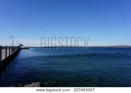 A view of Little Traverse Bay, and the Pierhead Lighthouse, as seen from the shore at Bayfront Park, adjacent to the Petoskey Municipal Marina, in Petoskey, Michigan, during October.