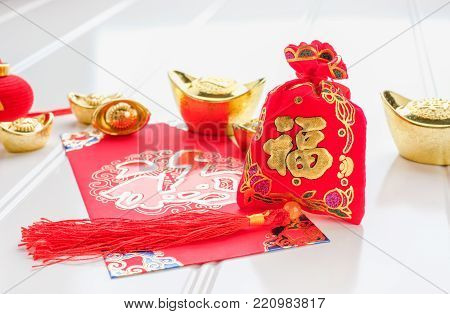 Chinese New year,ang pow red felt fabric bag with gold ingots and oranges and flower on white wood table top,Chinese Language mean Happiness and on ingot mean wealthy