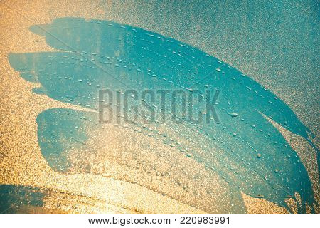 Close-up imprints of the fingers on the water dust sprayed window. Blue shades mixing with orange shades of shining setting down sun. Ideal background for illustrations, collages. Artistic retouching.