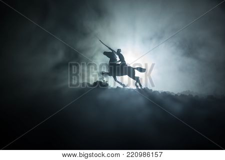 World War Officer (or Warrior) Rider On Horse With A Sword Ready To Fight And Soldiers On A Dark Fog