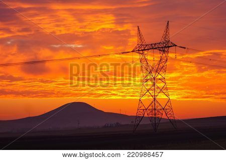 High voltage transfer lines and pylon at sunrise in a cloudy day