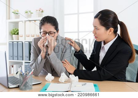 attractive female company manager sneezing and woman co-worker looking at her feeling afraid when they having meeting in office.