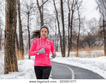 Winter running sport woman wearing jacket and smartwatch. Fit Asian runner jogging in winter forest doing outdoor run exercise. Active lifestyle.