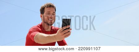 Young man taking selfie with phone using smartphone smiling at camera for self-portrait photo. Technology modern socia media lifestyle panoramic banner portrait.
