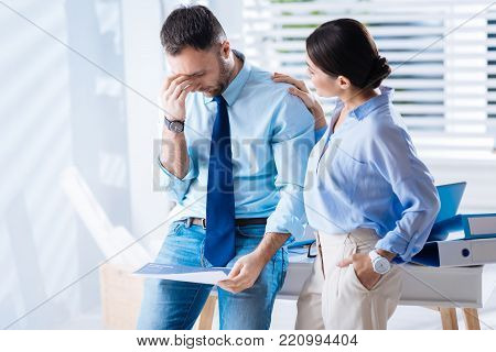 Attentive coworker. Exhausted emotional specialist standing with his hand touching the forehead and closing his eyes while a kind attentive supporting woman comforting him