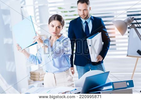 Looking irritated. Young clever emotional woman standing with a folder in her hands and frowning because of being irritated with her colleague standing behind her back