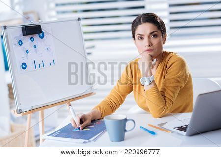 Smart employer. Calm responsible clever employer feeling confident while sitting at the table with her chin resting on the hand and looking in front of herself