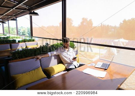 Caucasian real estate broker speaking by smartphone with customer and using laptop. Persistent young man dressed in classic style white shirt sitting on sofa and talking. Concept of apartments for rent and investments, good Internet connection for job.