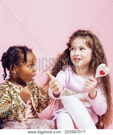 lifestyle people concept: diverse nation children playing together, caucasian girl with african little girl holding candy happy smiling close up on pink background