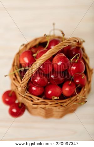 Cherries on a red plate on a light wooden background. Selective focus.