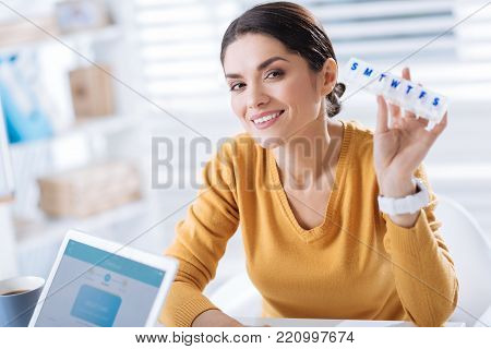 Cheerful woman. Recovered cheerful young woman sitting with a pillbox in her hand and feeling happy during her first working day after a long illness