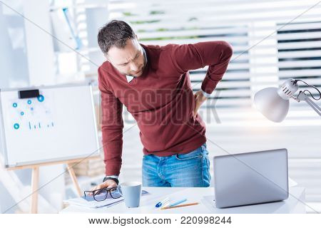 Backache. Young tired upset man looking at the screen of his laptop while standing near the table and having a strange backache
