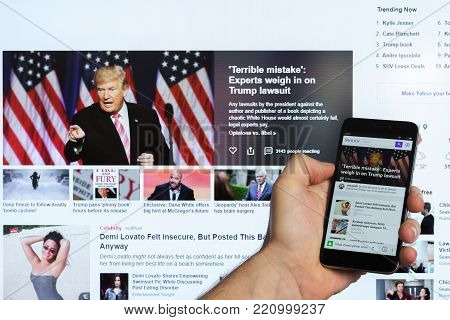 Adygea, Russia - January 5, 2018: the news feed of the popular Yahoo website of the Yahoo search engine on the screen of the Chinese smartphone Xiaomi in the male hand