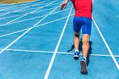 Runner athlete starting running at start of run track on blue running tracks at outdoor athletics and fiel stadium. Sprinter. Sport and fitness man lower body, legs and running shoes sprinting. poster