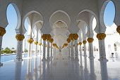 Architectural symmetry in a corridor of the Sheikh Zayed Mosque in Abu Dhabi, U.A.E. Blue skies and reflection in tile floor. White and gold architecture. House of Islamic worship for Muslim religion. poster
