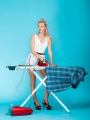 Full length sexy girl retro style ironing male shirt, woman housewife in domestic role. Traditional sharing household chores.  Pin up housework.  Vivid blue background poster