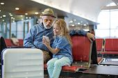 Look at this. Optimistic granddaughter is sitting on red bench at airport lounge with her grandfather while showing him screen of mobile phone. They are expressing interest while looking at display poster