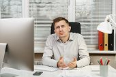 Shocked perplexed and stress business man in shirt sitting at the desk, working at computer with modern monitor, folders, lamp, documents in light office on window background. Manager or worker poster