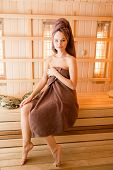 Young woman relaxing in a sauna dressed in a towel. Interior of new Finnish sauna, infrared panels for medical procedures, classic wooden sauna poster