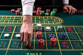A close-up vibrant image of green casino table with roulette, with the hands of croupier and multicolored chips, on black background. Casino. Gambling. Roulette. Betting poster