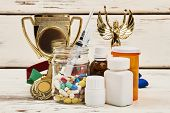 Trophies and diverse medicaments. Reaching victory by unfair play. Doping scandals and sport. poster